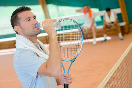Man on tennis court drinking from bottle of water