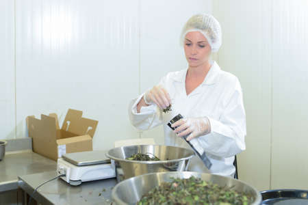 pouch: Woman packing ingredient into pouch Stock Photo