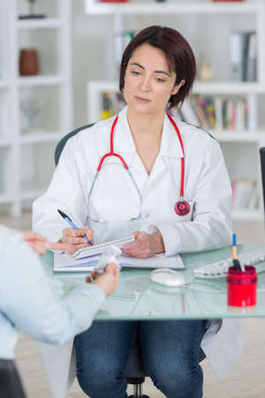 intoxication: sick female patient complaining of pain to doctor