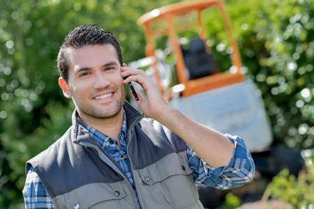 Gardener au téléphone, pelle en arrière-plan