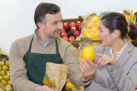 serf: smiling woman choosing different fruits at farm food store display
