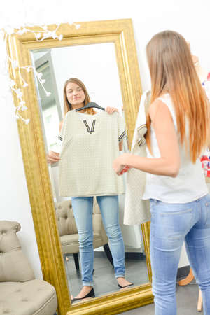 checkroom: Young woman trying on clothes Stock Photo