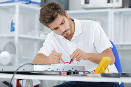 hobs: handsome electrician testing induction hobs Stock Photo