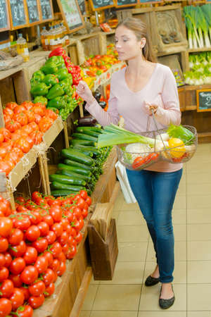 Woman proudly holding up a basket of vegetables Stock Photo