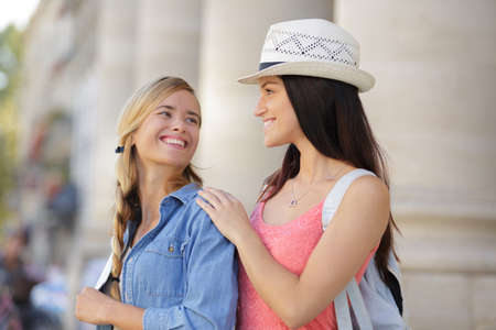 explores: happy girlfriends walking through town during vacation Stock Photo