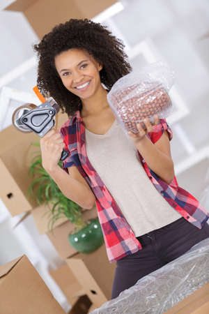young girl moving in apartment packing and taping boxes