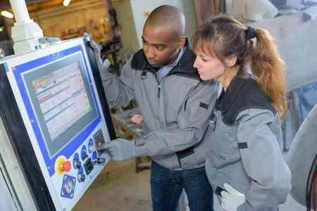 computerised: Industrial workers programming machine