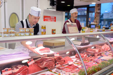 meat counter: butcher preparing meat behind counter Stock Photo
