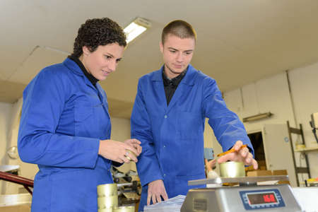 balanza de laboratorio: los trabajadores jóvenes de un peso objetivo Foto de archivo
