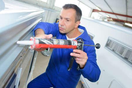 caulk: Mechanic applying sealant