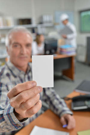 man holding card: man holding card in office