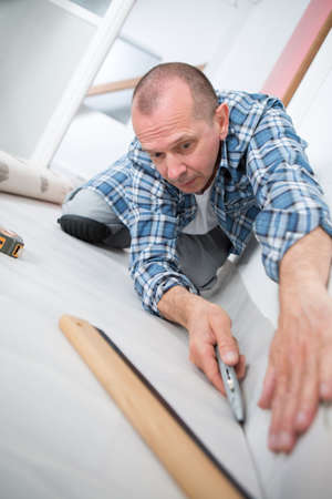 padding: handyman installing new layered wooden parquet Stock Photo