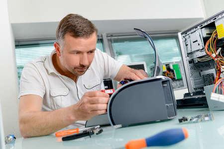 fixing: man fixing printer