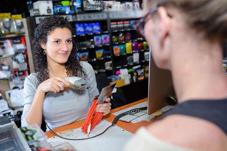 shop assistant: Shop assistant scanning product