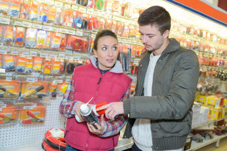 grease paint: young entrepreneur buying spray lubricant in hardwarestore Stock Photo