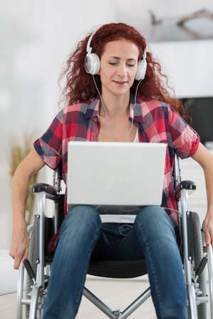 disabled woman with laptop and headphones relaxing at home