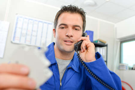 Man on telephone, holding unfocused electrical component Stock Photo