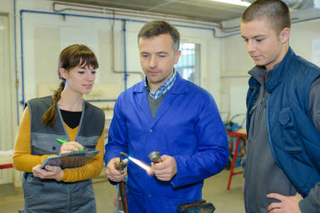 skilled labour: ironworks teacher showing students how to securely use gas welder