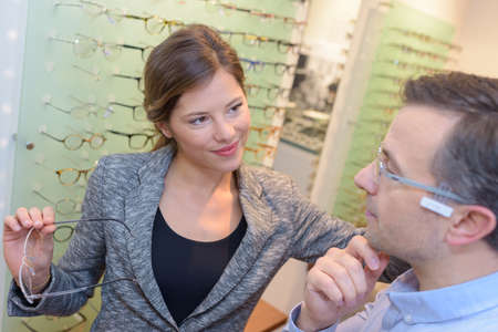 Optician helping customer choose spectacles Stock fotó
