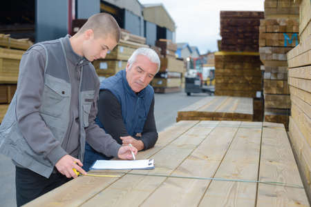 confer: Men looking at clipboard and measuring wood
