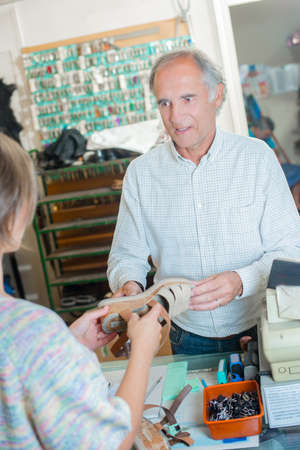 cobbler dealing with customer Stock Photo