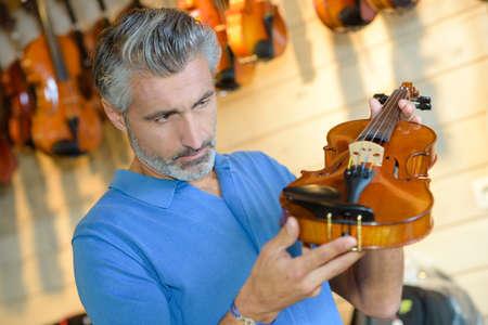 retailers: Man inspecting violin