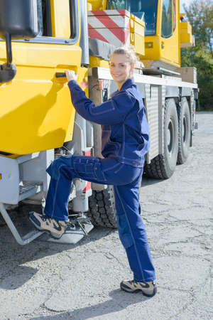 tow tractor: Woman stepping into cab of truck Stock Photo