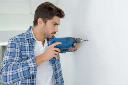 mid thirties: male builder drilling holes in wall at construction site