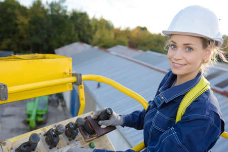 picker: woman maneuvering cherry picker above warehouses