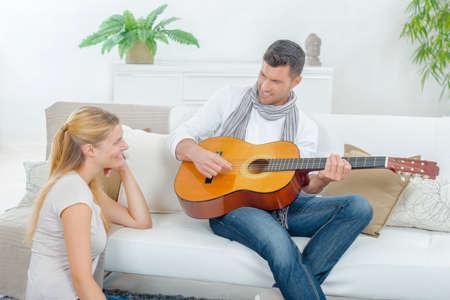 woo: Man playing guitar to lady
