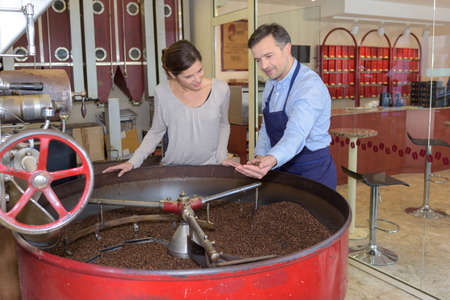 food industry: Man and woman looking into vat of coffee beans