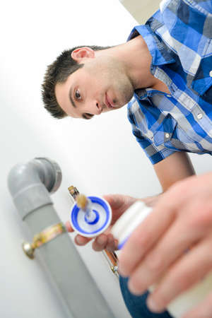 gluing: Plumber gluing a pipe Stock Photo