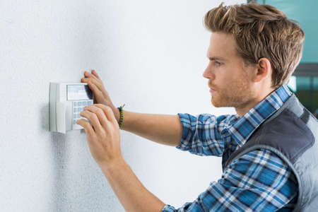 handsome young electrician repairing intercom Stock Photo