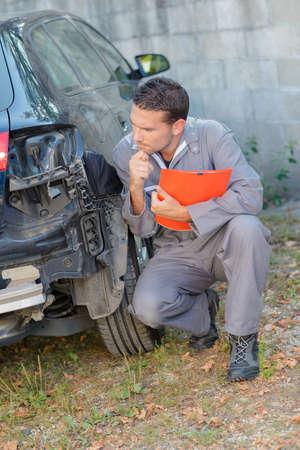 assessing: Mechanic assessing damage to rear of car