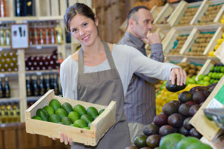 stacking: Woman stacking avocados in greengrocers