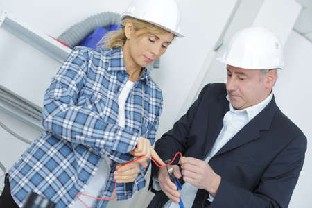 hard hats: businessman and female worker in hard hats at construction site Stock Photo