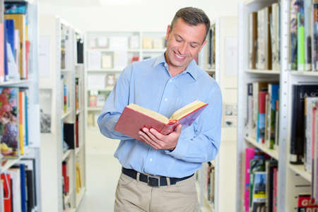 reading a book while standing up Stock Photo