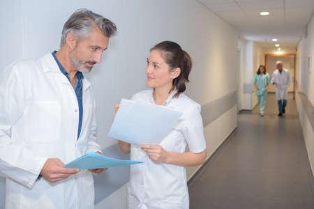 conversing: Medics conversing in hospital corridor