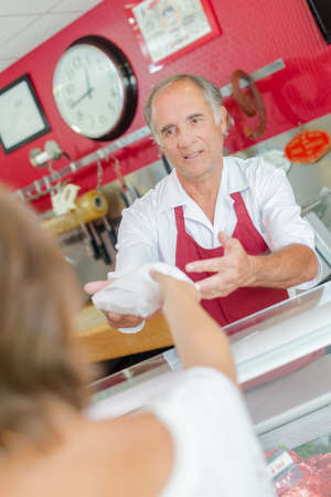 Butcher serving customer over counter Stock Photo