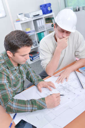 amend: Two men in hardhats looking at blueprints