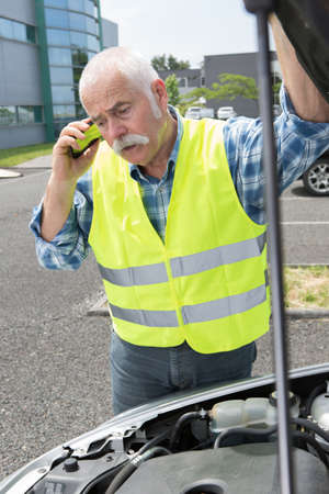 senior man on the phone looking at his broken car Stock Photo