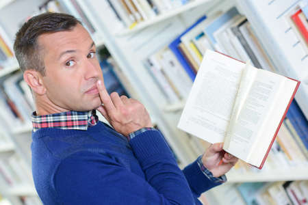 reprimand: Man in library making gesture for silence Stock Photo