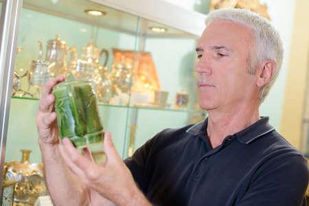 proprietor: Man holding old green teapot
