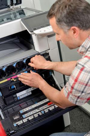 copy machine: man fixing photocopier