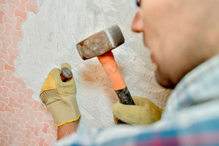 Man removing tiles from wall with hammer and chisel Stock Photo