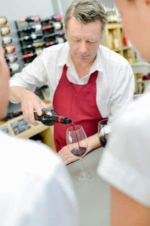 merchant: Wine merchant pouring some wine