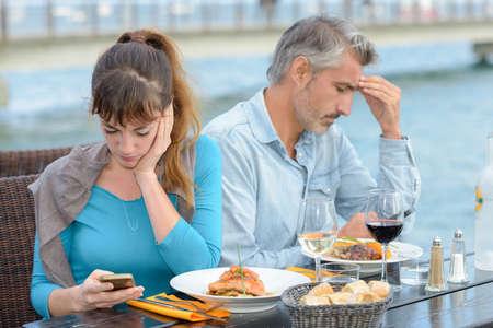 彼らの電話を見て両方の食事を持っているカップル