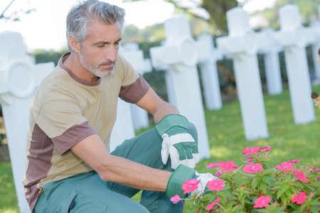 tending: Man tending flowers in graveyard