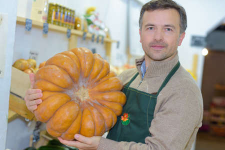 shopkeeper: Shopkeeper holding large squash Stock Photo