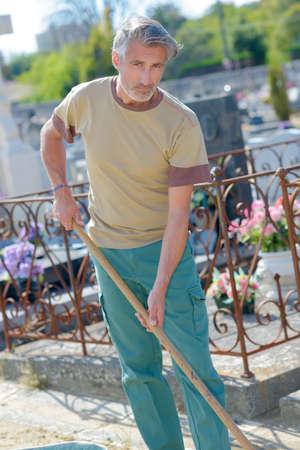 Maintenance man working in cemetery Stock Photo